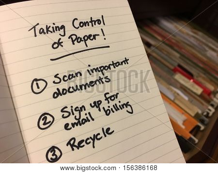Piles of paper in filing cabinet Taking control of paper to-do list hand written on notepad scan documents shred and recycle