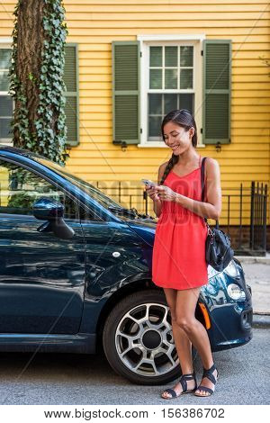 Asian woman using mobile phone app for car sharing service or city traffic information in front of her house. New car owner using phone to check status, control her new car. Smartphone taxi concept.