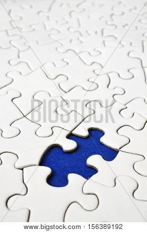 A low angle image of a white jigsaw puzzle with a single puzzle piece missing.