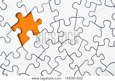 A top view image of a white jigsaw puzzle with a single puzzle piece missing.