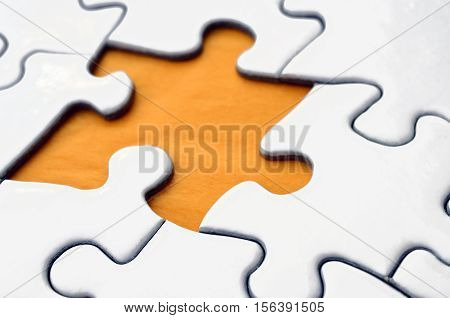 A close up view of a white jigsaw puzzle with one missing puzzle piece.