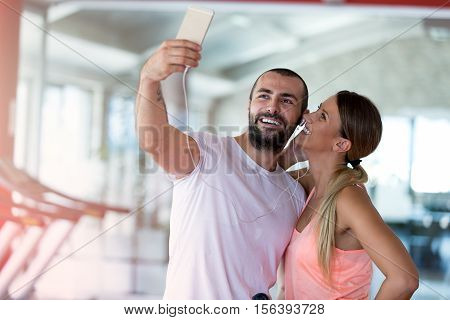 Young couple taking a sefie in a gym.