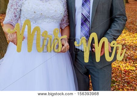 bride and groom holding Mr Mrs the bride and groom with the words Mr. and Mrs.