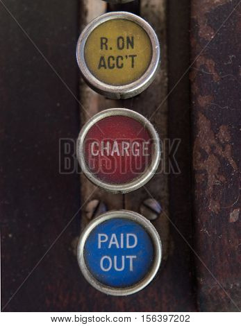 Close up of three keys, received on account, charge and paid out, on an antique wooden cash register using natural light and shallow depth of field. Dirt on round buttons from heavy use.