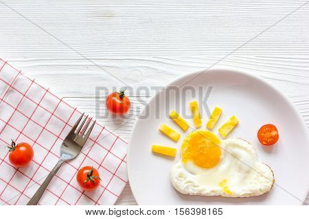 sunshine fried eggs breakfast for kid on wooden background top view