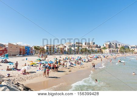 La Vila Joiosa - August 25, 2016; Summer on crowded Mediterranean beach scenes La Vila Joisoa with multi-colored houses that line the road behind beach Alicante Spain