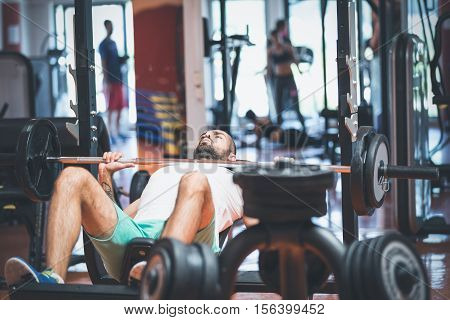 Portrait of a handsome male bodybuilder doing bench press in fitness gym.