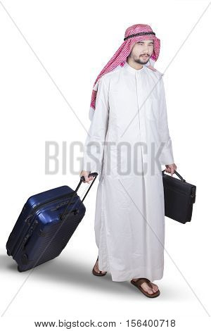 Arabian entrepreneur carrying a briefcase and suitcase while walking in the studio isolated on white background
