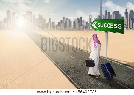 Back view of arabian businessman walking on the highway with success text on the signpost while carrying a suitcase and a briefcase