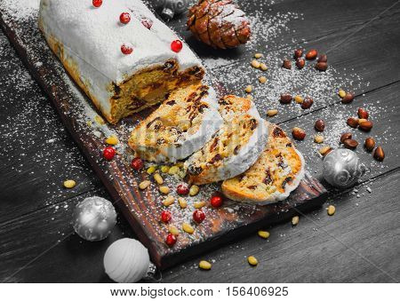 Christmas stollen. Traditional German European festive dessert. Ingredients cranberries pine nuts for Christmas Stollen. Stollen cake cut into pieces. Christmas food card. Dark Black background