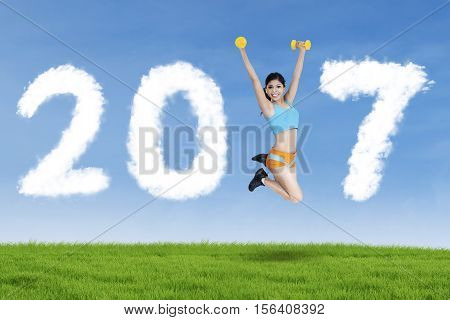 athlete female lifting two dumbbell and leaping on the meadow while forming numbers 2017 on blue sky