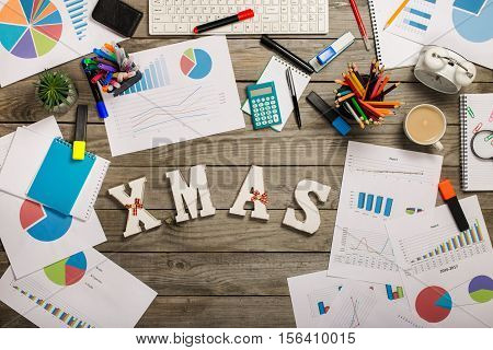 Word xmas with different charts and office objects on the wooden desk top view