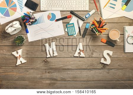 Word - Xmas on the wooden desk with different annual reports and office objects top view with copy space