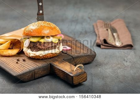 Beef fresh burger with fries on the old board with copy space close up