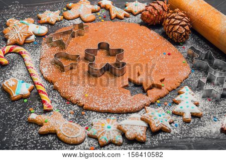 Cooking Christmas cookies gingerbread. On a dark brown background gingerbread dough. Forms for Christmas cookies gingerbread rolling pin cones. Cookies with icing. Christmas New Year card.