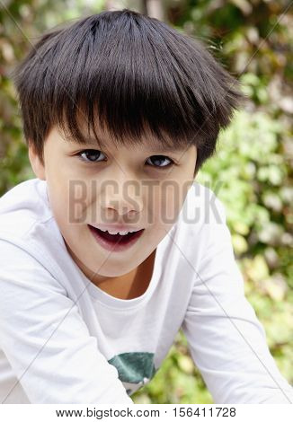 Portrait of a Boy with Dark Hair Outdoors