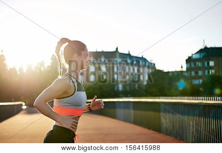 Woman Running In The Late Afternoon On Empty Road