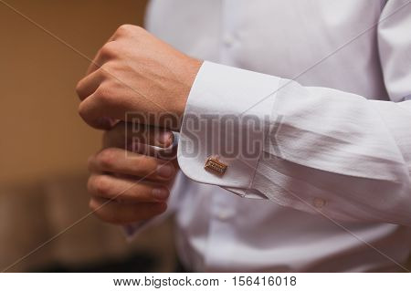 Groom buttons cuffs on the shirt close-up. Wedding day.