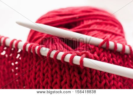 Knitting needles and bordo ball of yarn on white background. Close-up of handmade knitted cloth with tools. Handiwork, leisure, hobby concept