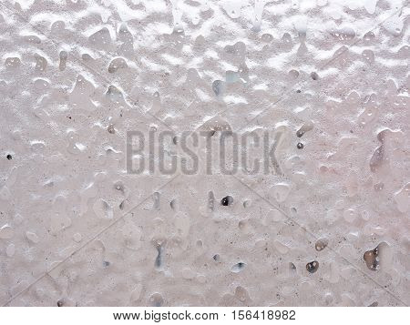 Texture of ice and drops on window glass in inclement winter weather. Close up. Icy rain background