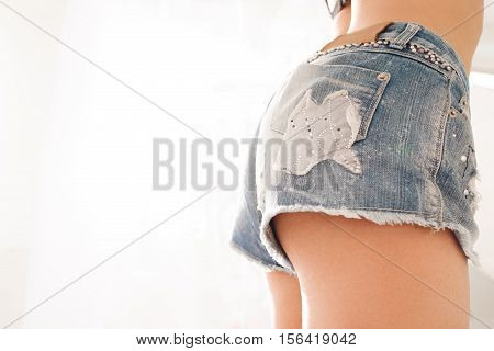 Profile of woman butt in denim shorts, free pace. Side view on perfect buttocks of young girl in jeans briefs, copy space on white background