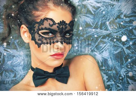 Beautiful woman with carnival mask looking, christmas night. Cristmas party. Secret. Fashion. Venetian carnival. Hot babe. Ice winter background