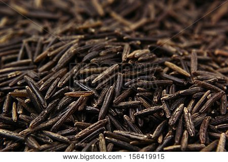 Black rice close-up background. Heap wild brown unpolished rice for vegetarians. poster