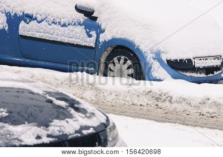 The parked city car brought by snow on the crude road.