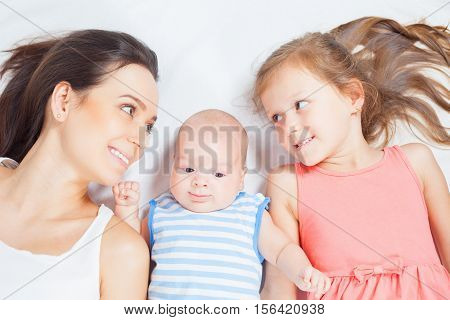 Happy family, mother with daughter looking at baby. Newborn and child. Mothercare is most important in children life.
