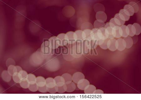 Vintage blur bokeh defocused purple colorized lights on dark room background. Christmas abstract blur background brown-red lights bokeh of Xmas tree at night party in winter, vintage color toned