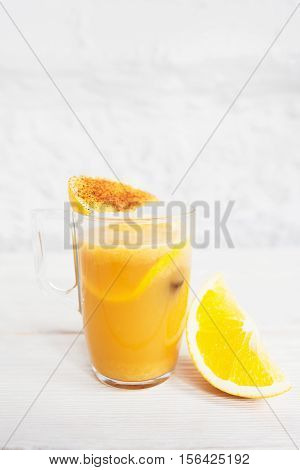 Cocktail glass with refreshing orange punch on white background. Fruit sangria with citrus slices, free space for text. Refreshment, party, relaxation concept