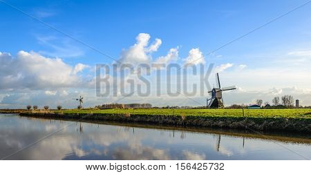 Panoramic image of a historic wooden holllow post mill and a small metal mill in a colorful lanscape in the Netherlands. It's a sunny day in the end of the Dutch winter season.