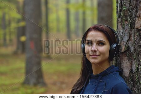 Beautiful and happy girl listens to music in headphones in nature. Autumn forrest in the background