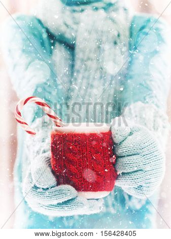 Woman holding winter cup close up on light background with snowfall. Woman hands in teal gloves holding a cozy mug with hot cocoa, tea or coffee and a candy cane. Winter and Christmas time concept.