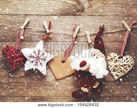 Festive Christmas decoration over wooden board background with snowfall.