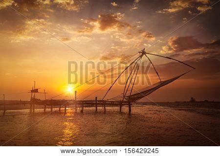 Kochi chinese fishnets on sunset. Fort Kochin, Kochi, Kerala, India. With light leak and lens flare