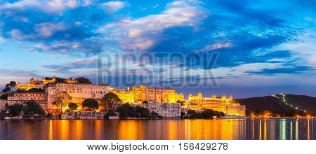 Panorama of famous romantic luxury Rajasthan indian tourist landmark - Udaipur City Palace in the evening twilight with dramatic sky - panoramic view. Udaipur, India