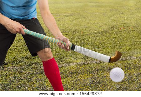 men battle for control of ball during field hockey game