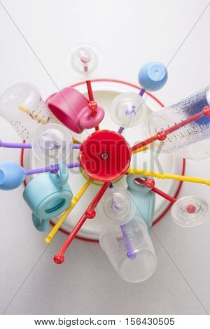 Baby drainer full of plastic tableware objects as baby bottles. High view angle