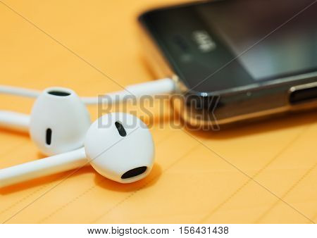 Ear phone into smart phone mobile on blurred background
