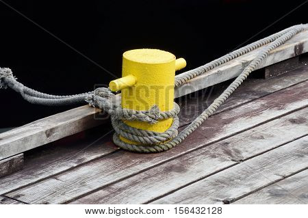 Yellow boat tying post with rope on wooden decking