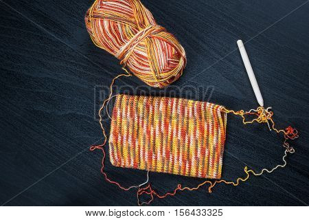 Skein of thread and a crochet hook with case on black background