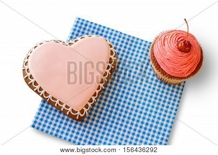 Heart cookie and pink cupcake. Pastry on blue checkered napkin. Small holiday for loved ones. Find joy in the ordinary.