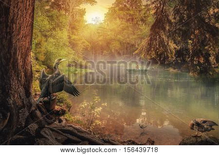 fisherman in a boat on calm misty lake