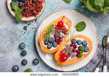 Clean food for diet. Papaya with yogurt and multi fruit, chia seeds, blueberry and goji berries on plate over concrete background. top view
