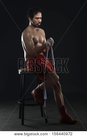 Athlete Man Asian Boxer Sitting In The Chair While Wearing White Strap