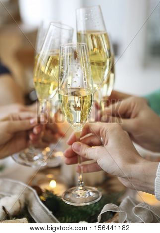 Group of friends toasting with champagne while having Christmas dinner. Close up
