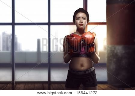 Young Asian Woman Posing With Boxing Gloves In Her Chest