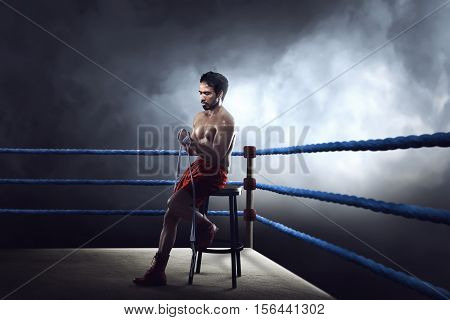 Sporty Asian Boxer Man Sitting On Ring While Wearing Strap