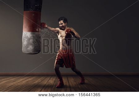 Powerful Asian Male Boxing Exercising With Punching Bag